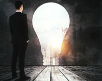 Opportunity concept. Side view of thinking young businessman standing in abstract room with light bulb opening, city view and daylight. Opportunity concept. 3D Royalty Free Stock Photos