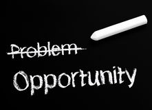 Opportunity rather than a problem. Stick of chalk with problem crossed out leaving the word opportunity Stock Photo
