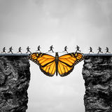 Opportunity And Transition Concept. Or migration as a butterfly acting as a bridge between two cliffs for people to go to their journey as a symbol for hope and Royalty Free Stock Photo