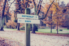 Opposite directions towards difficult and easy. Signpost in a park or forested area with arrows pointing two opposite directions towards difficult and easy Stock Photos