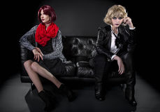 Opposite Fashion Styles. Conservative female model snobbish to a younger model in goth punk fashion clothing stock photo