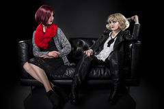 Opposite Fashion Styles. Conservative female model snobbish to a younger model in goth punk fashion clothing royalty free stock photography