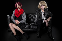 Opposite Fashion Styles. Conservative female model snobbish to a younger model in goth punk fashion clothing royalty free stock photos