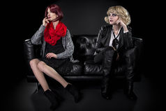 Opposite Fashion Styles. Conservative female model snobbish to a younger model in goth punk fashion clothing royalty free stock image