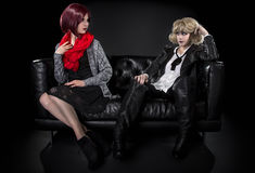 Opposite Fashion Styles. Conservative female model snobbish to a younger model in goth punk fashion clothing stock images