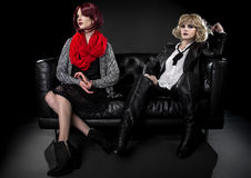 Opposite Fashion Styles. Conservative female model snobbish to a younger model in goth punk fashion clothing stock photography