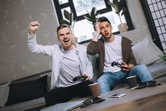 Gamers playing party. The opposite picture of two gus playing game. This time the gus on the left has one while the other one has lost. He can`t believe he could Royalty Free Stock Image