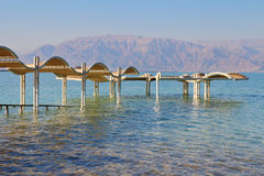 The opposite shore -Jordanian mountains. Sunny beach on the Dead Sea. A wonderful warm day in December. The beach pavilion is half flooded with seawater risen Royalty Free Stock Photo