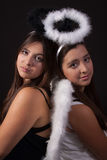 Opposite twins. Two identical twin sisters wearing white and black angel halos posing together over black Stock Photography