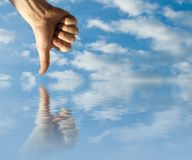 Opposites. Hand in the sky and his reflex in the water stock photo