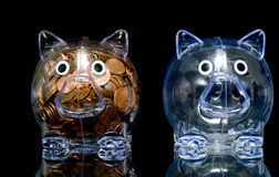 Opposites. Two clear acryllic piggy banks one stuffed full of american pennies the other empty, Illustration of the haves and the have nots Royalty Free Stock Photos