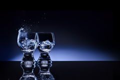 Opposites attract!. A picture of two shaped transparent shot glass with choppy liquid and ice Stock Images