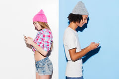 Opposites attract. Funky young couple holding mobile phones and standing back to back while standing against colorful background royalty free stock photos