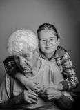 Opposites attract. Portrait of a little girl with her great-grandmother - opposites attract- old-young, woeful-blessed,in doubt-safety, contemplative - smiling royalty free stock photo