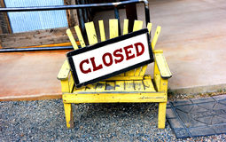 Opposites Attract. A yellow wooden bench sits besides a welcome mat in front of a cafe. The opposites come in with a sign on the bench that states closed. The royalty free stock photography