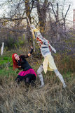 Opposition. Man in the guise of a mummy on falls on the girl witch with red hair Stock Photos