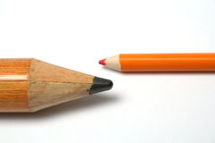 Opposition of a small and greater pencil. On a horizontal Royalty Free Stock Photo