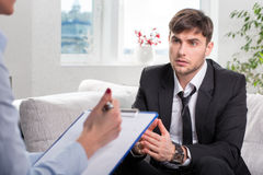 Oppressed man talking with psychologist Royalty Free Stock Photography