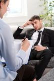 Oppressed man talking with psychologist Royalty Free Stock Images