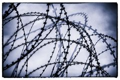Oppressive Razor Wire. Used to entangle people from getting through or over a barrier Royalty Free Stock Photo