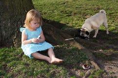 Opps! trauriges kleines Mädchen mit Hund und Eiscreme Stockfotografie