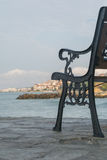 Opróżnia ławkę na kamiennym bulwarze nad błękitnym morzem Zdjęcia Stock