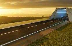 Opróżnia asfaltową drogę z tunelem, greenfield i nowożytną miasto linią horyzontu, zdjęcia stock