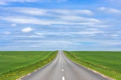 Opróżnia asfaltową wiejską drogę w górę wzgórza z zielonej trawy polami pod białym niebieskim niebem w lecie i chmurami Obrazy Royalty Free