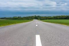 Opróżnia asfaltową wiejską drogę z zielonej trawy polami pod burzowymi chmurami w lecie Zdjęcia Stock