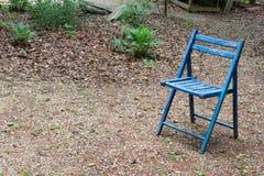 Opróżnia błękitnego falcowania krzesła outdoors, kopii przestrzeń, śmiertelny żal nieobecności pojęcie fotografia stock