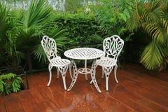 Opróżnia białego dokonanego żelaza ogródu herbacianego stół i krzesła w patiu po deszczu obraz royalty free