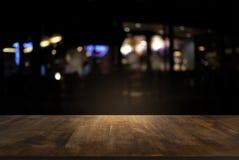 Opróżnia ciemny drewniany stół przed abstrakt zamazującym backgrou zdjęcie stock