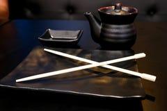Opróżnia czerń jasnego ustawiającego dla suszi, talerz z Japońskim chopstick, spodeczek na czarnym stole obraz royalty free