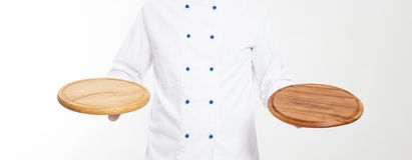 Opróżnia deski dla pizzy w rękach szef kuchni odizolowywający obrazy royalty free