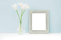 Opróżnia drewnianą ramę i kwiaty w wazie na stole na błękitnym tle Egzamin próbny Up Zdjęcia Stock