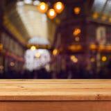 Opróżnia drewnianego pokładu stół nad zamazanym bokeh zakupy centrum handlowego abstrakta tłem Zdjęcie Royalty Free