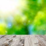 Opróżnia drewnianego pokładu stół z ulistnienia bokeh tłem. Zdjęcia Stock