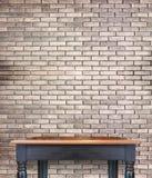 Opróżnia drewnianego rocznika stół na ceglanej płytki ścianie, egzamin próbny up displ dla obrazy stock