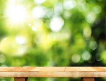Opróżnia drewnianego stół i zamazującego ogrodowego bokeh światła tło Mo obrazy royalty free