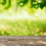 Opróżnia Drewnianego stół w ogródzie z Jaskrawym - zielony tło