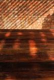 Opróżnia Drewnianego stół z ściana z cegieł i światła słonecznego cieniem Obrazy Stock