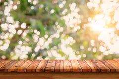 Opróżnia drewnianego stół z bokeh abstrakta zieleni tłem Obrazy Stock