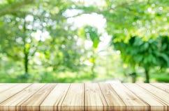 Opróżnia drewnianego stołowego wierzchołek z zamazanym zielonym naturalnym tłem fotografia royalty free