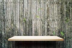Opróżnia drewnianego szelfowego pokazu z płotowym tłem Obrazy Royalty Free