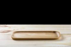 Opróżnia drewnianego talerza na drewno stole odizolowywającym na czerni Fotografia Stock