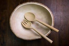 Opróżnia drewno talerza set z rozwidleniem i łyżka na drewnianym ciemnego brązu stole Obrazy Royalty Free