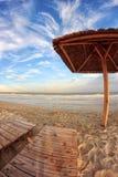 Opróżnia krzesła pod pokrywającymi strzechą parasolami na piaskowatej plaży Szeroka Kąta Vertical Fotografia zdjęcia royalty free