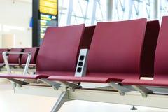 Opróżnia krzesła z elektrycznym ujściem w lotniskowej czekanie terenu pobliskiej bramie Zdjęcie Stock