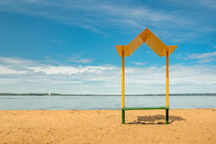 Opróżnia plażę z ławką z baldachimem na wybrzeżu Zdjęcia Royalty Free