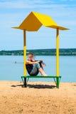 Opróżnia plażę z ławką z baldachimem na wybrzeżu Zdjęcia Stock